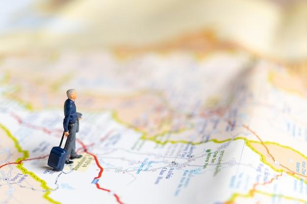 Gente di affari in miniatura in piedi sulla mappa, concetto di viaggio