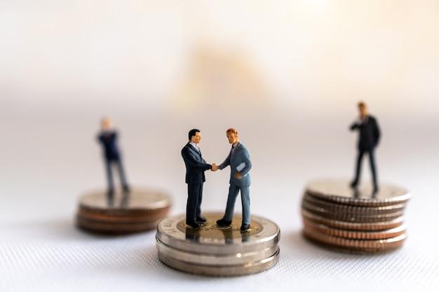 Stretta di mano in miniatura dell'uomo d'affari con la pila di monete sulla mappa del mondo, gli investimenti e il concetto di business