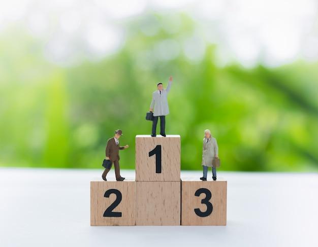 Uomo d'affari miniatura che sta su un podio dei vincitori di legno con il numero nero.