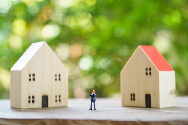 Uomini d'affari in miniatura in piedi analisi degli investimenti alloggi o investimenti in beni mobili.