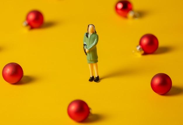 Stand di un uomo d'affari in miniatura circondato da palline di natale rosse su una superficie gialla