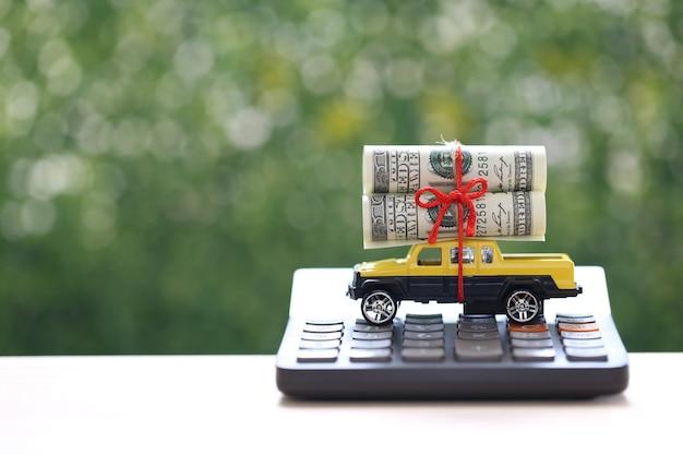 Auto in miniatura e banconote sulla calcolatrice con sfondo verde natura, risparmio di denaro per auto, finanza e prestito auto, concetto di investimento e business
