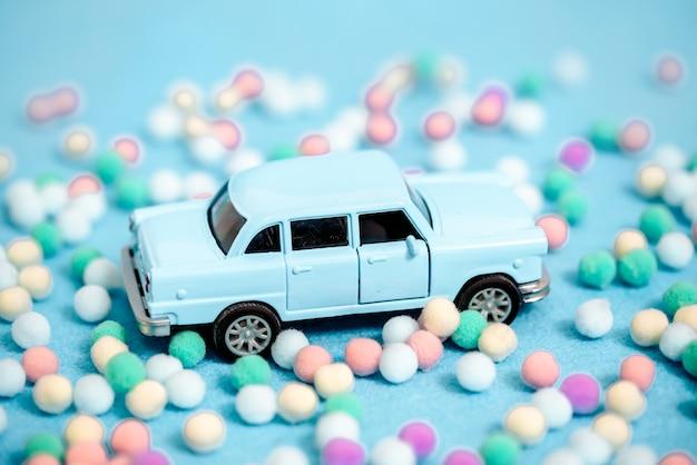 Auto in miniatura che trasporta un albero di natale su sfondo blu