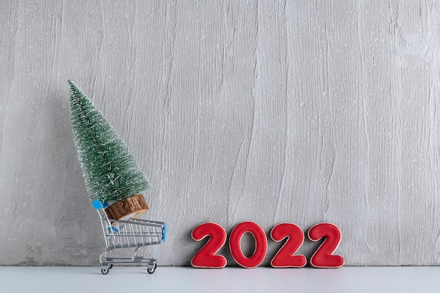 Albero di natale in miniatura nel carrello sullo sfondo dell'iscrizione 2022. acquisto e affitto di alberi di natale.