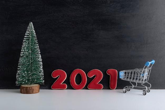 Albero di natale in miniatura, carrello del carrello e iscrizione 2021 su sfondo nero. sconti di capodanno, shopping.