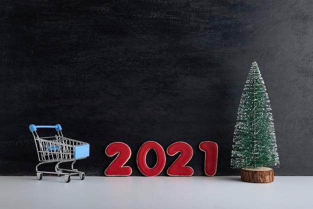 Albero di natale in miniatura, carrello del carrello e iscrizione 2021 su sfondo nero. acquisti di capodanno.