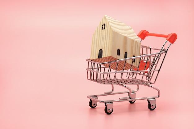 Casa in legno decorativa in miniatura nel carrello della spesa in vendita e acquisto rosa concept