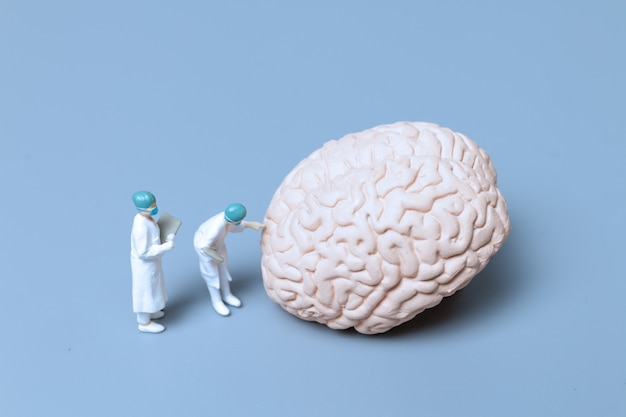 Medico in miniatura che controlla e analizza il morbo di alzheimer e la demenza del concetto di cervello, scienza e medicina