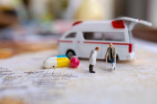 Medico e paziente in miniatura in piedi con la capsula e l'ambulanza. concetti sanitari.