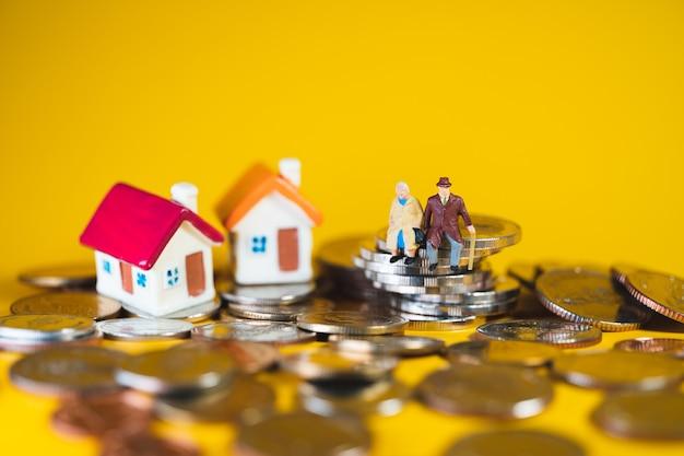 Anziani in miniatura che si siedono sulle monete della pila e sulla mini casa usando come concetto di pensionamento, affari e assicurazione di lavoro