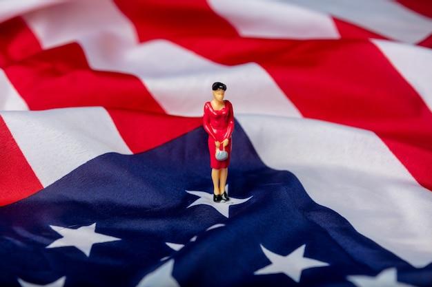 Figura in miniatura di una donna politica sulla bandiera degli stati uniti