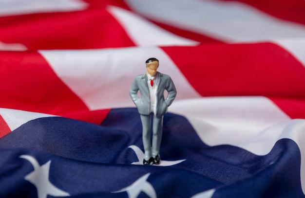 Figura in miniatura di un uomo politico sulla bandiera degli stati uniti