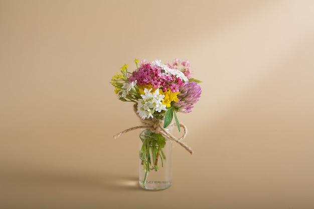 Bottiglia di vetro in miniatura con fiori di campo su fondo beige per congratulazioni per l'8 marzo, pasqua, festa della mamma