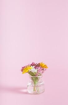 Bottiglia di vetro in miniatura con fiori di campo su uno sfondo rosa copia spazio per congratulazioni per l'8 marzo, pasqua, formato verticale per la festa della mamma
