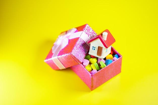 Casa in miniatura in confezione regalo su sfondo giallo utilizzando come proprietà immobiliare e concetto di famiglia