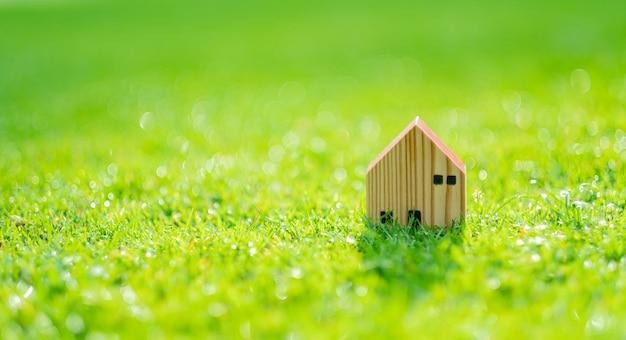 Modello di casa in miniatura su sfondo di erba