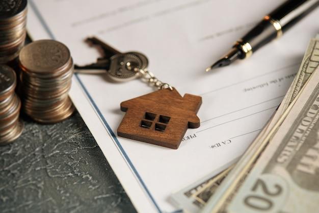Casa in miniatura con soldi e documenti fiscali.