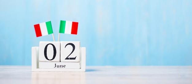Bandiera dell'italia in miniatura con calendario di giugno su tavolo bianco e sfondo blu della parete