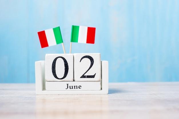 Bandiere dell'italia in miniatura con calendario di giugno su tavolo bianco e sfondo blu della parete