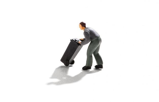Uomo in miniatura che spinge un bidone della spazzatura nero