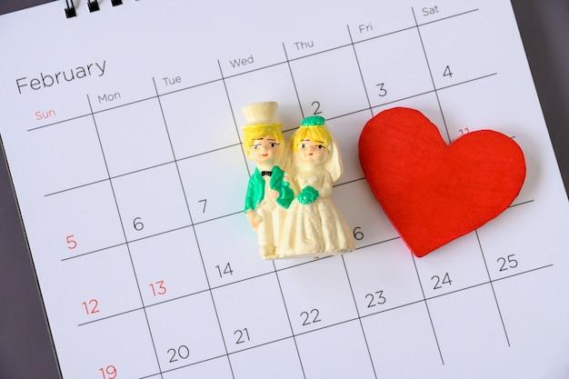 Coppia di sposi in miniatura sul calendario. concetto per matrimonio e san valentino.