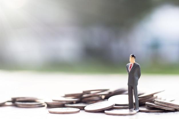 Modello in miniatura di uomo d'affari su una pila di monete.