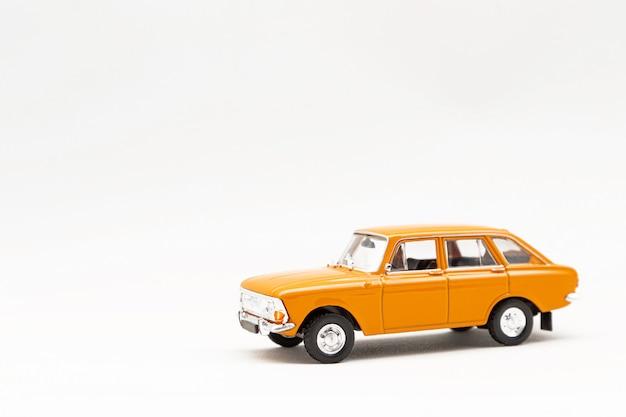 Modello in miniatura di un'auto retrò gialla su una superficie bianca