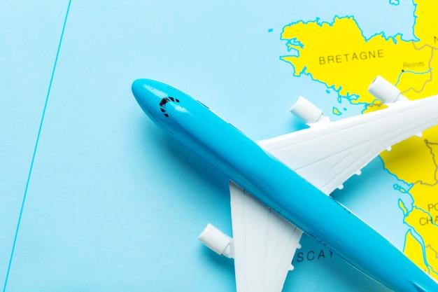 Miniatura di un aereo passeggeri che vola su una mappa Foto Premium