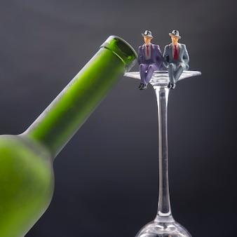 Persone in miniatura. concetto di problema di dipendenza da alcol. due uomini si siedono sul bordo di un bicchiere di vino vicino alla bottiglia