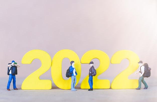 Viaggiatore con zaino e sacco a pelo in miniatura in piedi sul numero di legno 2022, felice anno nuovo concept