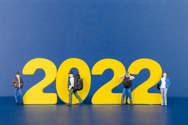 Persone in miniatura zaino in spalla in piedi sul numero di legno 2022, felice anno nuovo concept happy