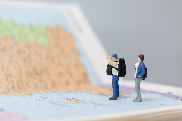 Persone in miniatura zaino in spalla che cammina sulla mappa concetti di viaggio e avventura.