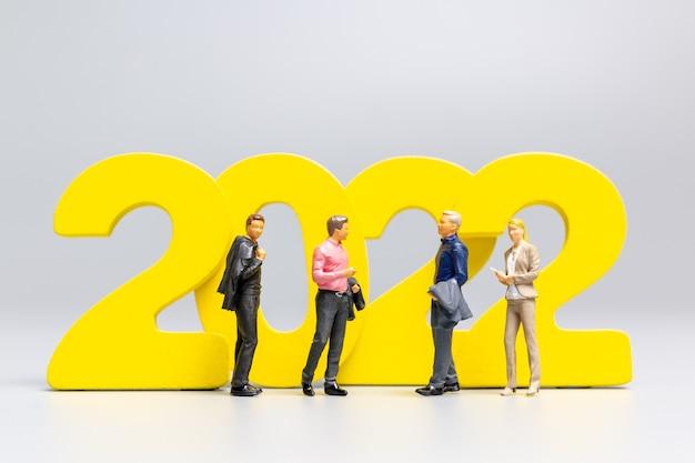 Persone in miniatura: uomini d'affari in piedi sul numero 2022, concetto di felice anno nuovo