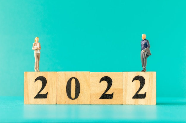 Persone in miniatura: uomini d'affari in piedi sul blocco di legno numero 2022, concetto di felice anno nuovo
