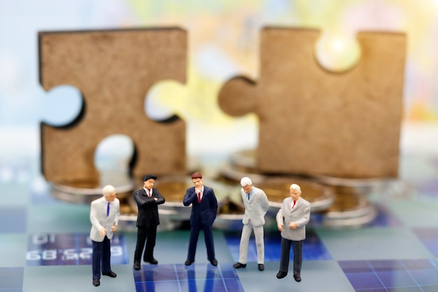 Persone in miniatura, uomo d'affari stanno pensando con il puzzle sulla pila di monete.