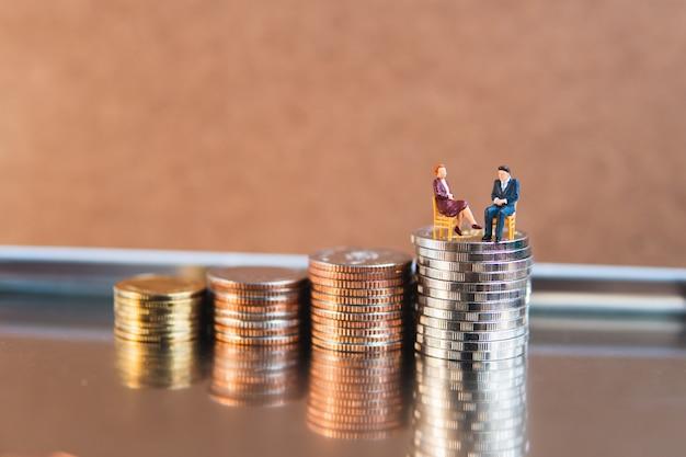 La gente, l'uomo d'affari e la donna di affari miniatura che si siedono sulla pila conia usando come lavoro di squadra di affari e concetto finanziario