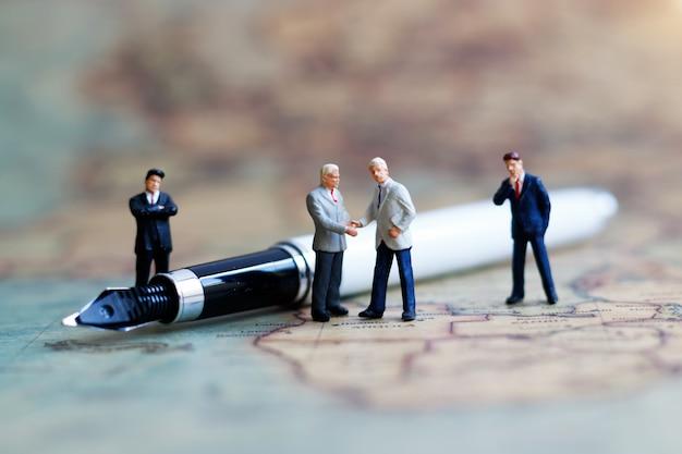 Persone in miniatura: stretta di mano dell'uomo d'affari sulla mappa del mondo con la penna. concetto di impegno, accordo, investimento e partenariato