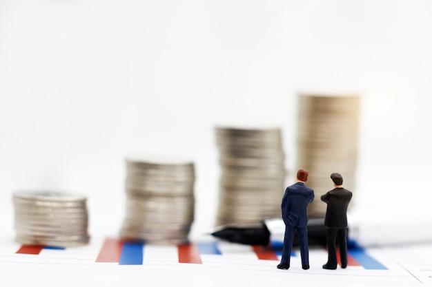 Persone in miniatura: uomo d'affari in piedi sul grafico con lo sguardo e il pensiero di pila di monete.