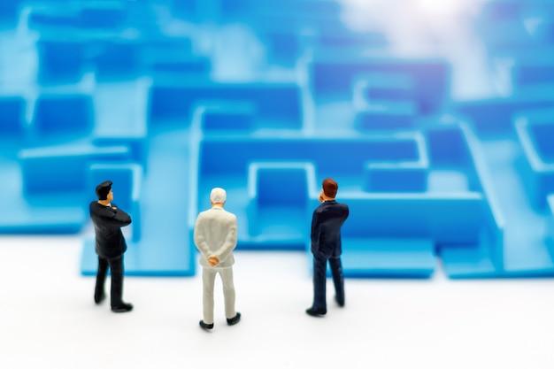 Persone in miniatura: uomo d'affari in piedi all'inizio del labirinto.