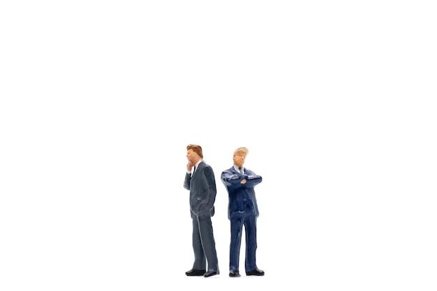 Persone in miniatura, uomo d'affari in piedi sul muro bianco