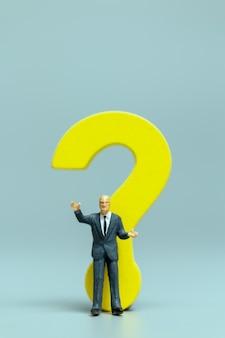 Persone in miniatura, uomo d'affari con una grande domanda. lavoratori che cercano di risolvere il concetto di problema