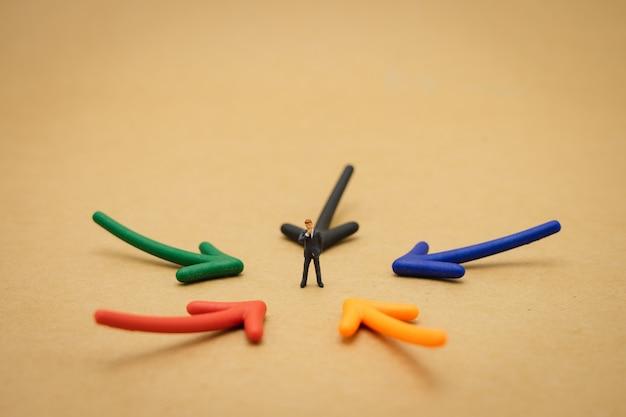 Uomini d'affari in miniatura che stanno in piedi analisi degli investimenti o investimento nel pensare