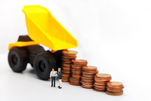 Persone in miniatura: uomini d'affari in piedi con pila di monete, finanza, investimenti e crescita nel concetto di business.