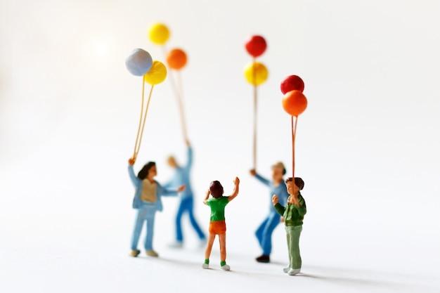 Bambini miniatura della gente che tengono pallone con luce solare, concetto felice di giorno della famiglia.