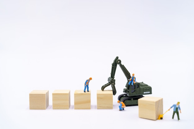 Persone in miniatura operaio edile gestisci i prodotti con il blocco di legno