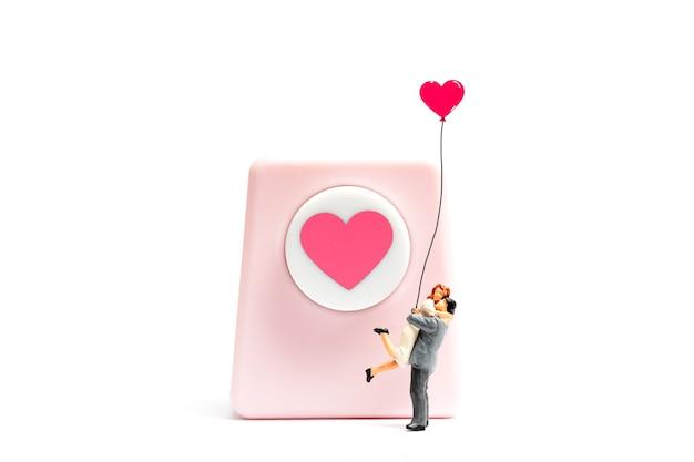 Coppia di persone in miniatura che abbraccia e tiene il palloncino