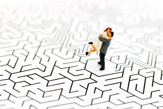 Persone in miniatura amante delle coppie in piedi al centro del labirinto, risolvi i problemi con amore.