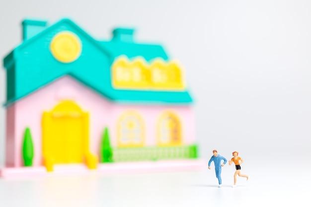Persone in miniatura, coppia che corre vicino alla loro casa insieme, concetto di stile di vita sano