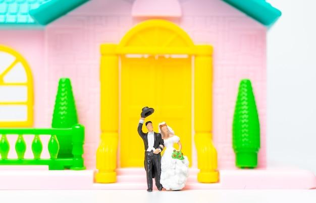Persone in miniatura, coppia in piedi insieme davanti alla loro casa