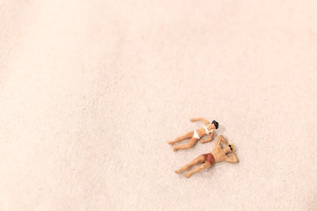 Persone in miniatura, coppia a prendere il sole insieme sulla spiaggia